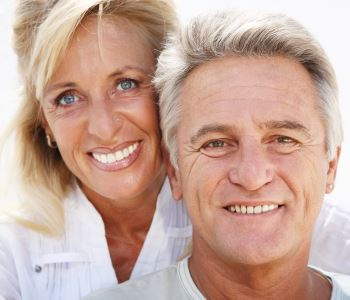 man and woman smiling with beautiful teeth after dental implant from Dr. David Spilkia