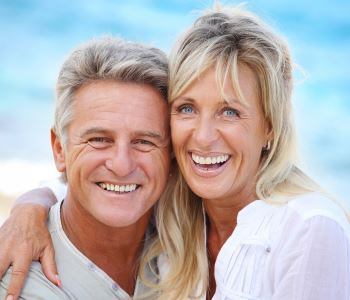 man and woman smiling with beautiful teeth after treatment