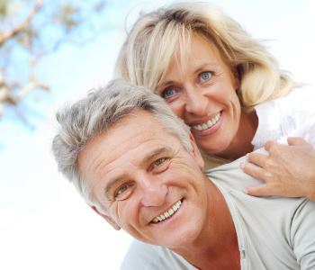 man and woman smiling with beautiful teeth after dental implant