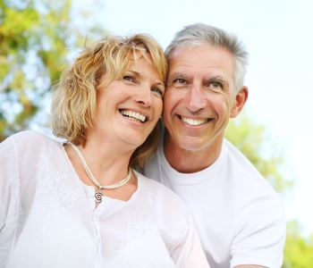 man and woman smiling with beautiful teeth after dental implants
